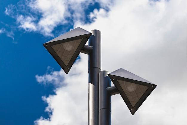 Postes de luz de forma triangular contra un cielo nublado azul. arquitectura urbana.