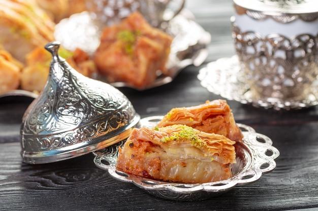 Postre árabe turco baklava con miel y nueces en una placa de plata