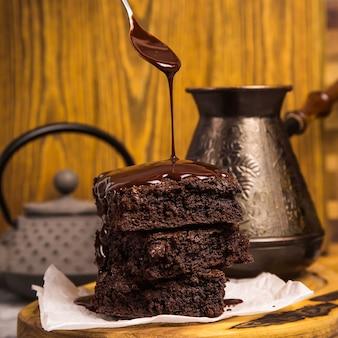 Postre brownie de chocolate entre tablas de madera oscura