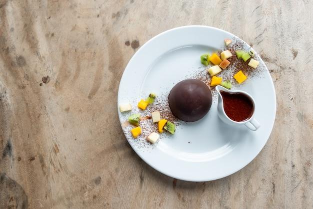Postre de chocolate cacao con rodajas de frutas.