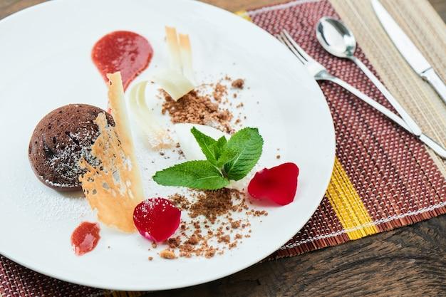 Postre de chocolate dulce y helado con cobertura de fresa en plato blanco
