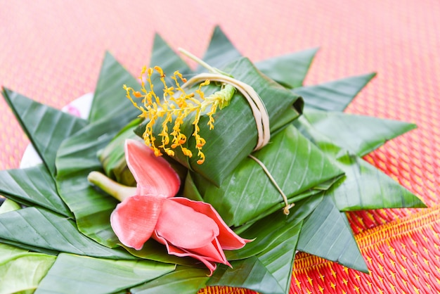 Postre comida tailandesa envoltura con hojas de plátano y flores