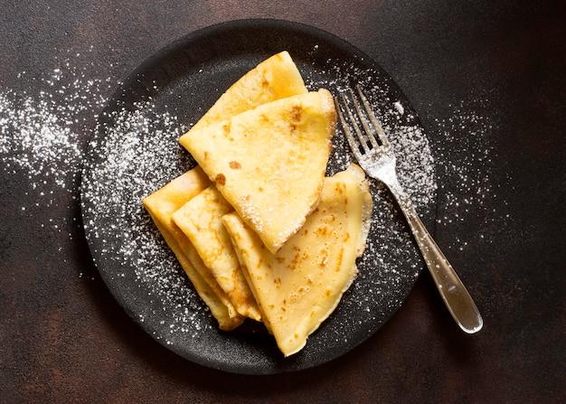 Postre de crepe de invierno delicioso y vista superior de azúcar