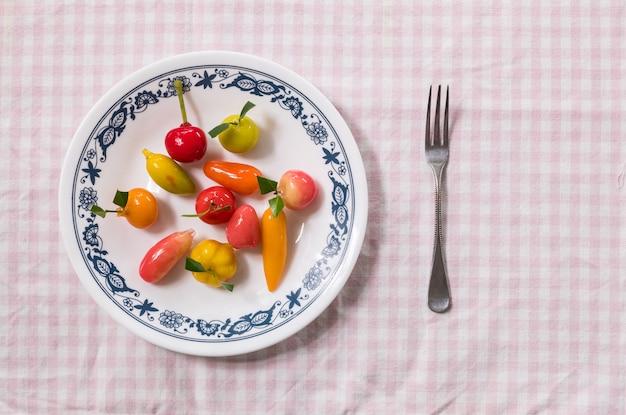 El postre dulce en forma de la fruta en plato con la bifurcación pequeña en fondo rosado de la servilleta