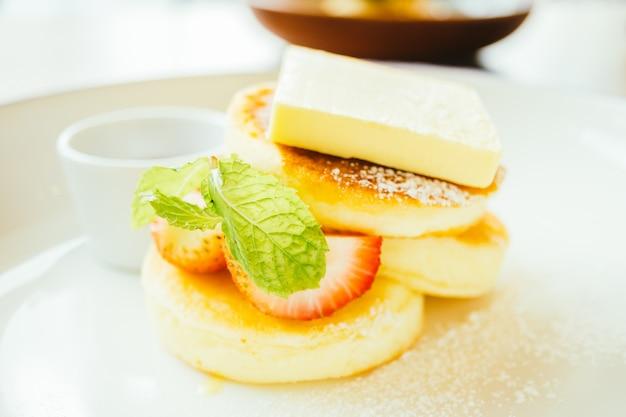 Postre dulce de panqueques con mantequilla y fresa.