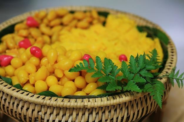 Postre dulce tailandés hecho por huevo york decorado con hojas en bandeja de madera de ratán