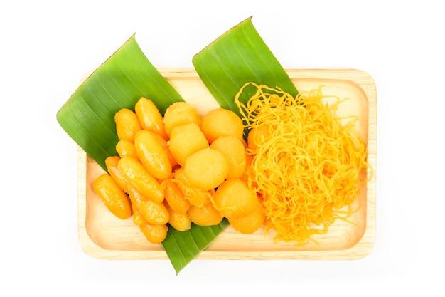 Postre dulce tailandés (med khun, thong yod, foy thong) en una placa de madera con hoja de plátano verde aislado sobre fondo blanco, postres tradicionales tailandeses