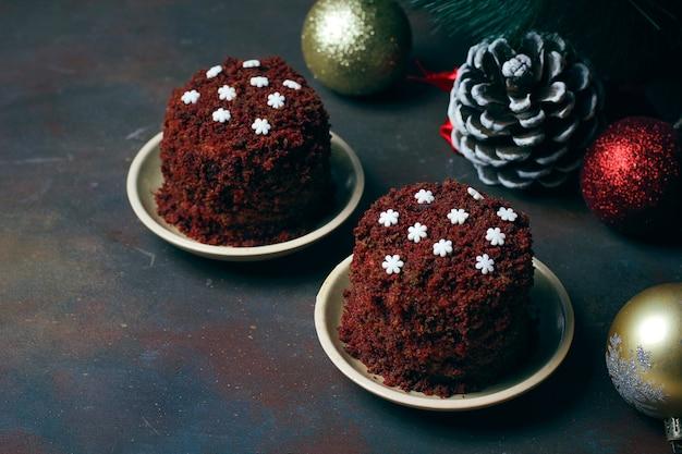 Postre festivo pastel de terciopelo rojo marrón con copos de nieve de caramelo blanco