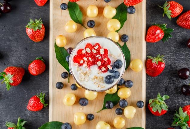 Postre con fresa, arándano, cereza, hojas en un jarrón sobre tabla gris y tabla de cortar, plano.