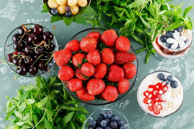 Postre con fresa, arándano, menta, cereza en florero y copa