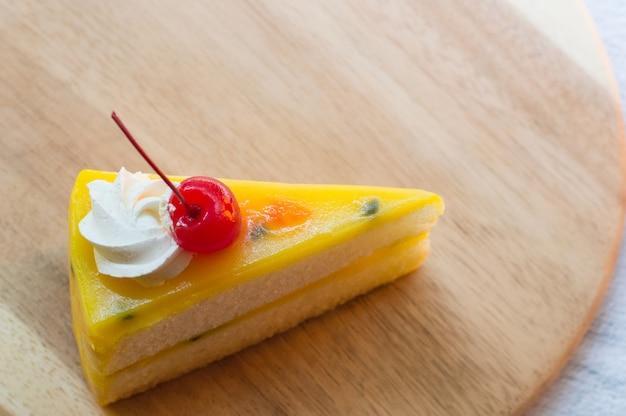 Postre fresco de la torta de la fruta de la pasión en la placa de madera