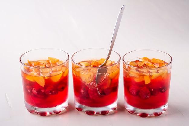 Postre de gelatina con frutas albaricoque frambuesa en tres vasos con una sola cuchara amarillo rojo verano blanco superficie aislada en fila