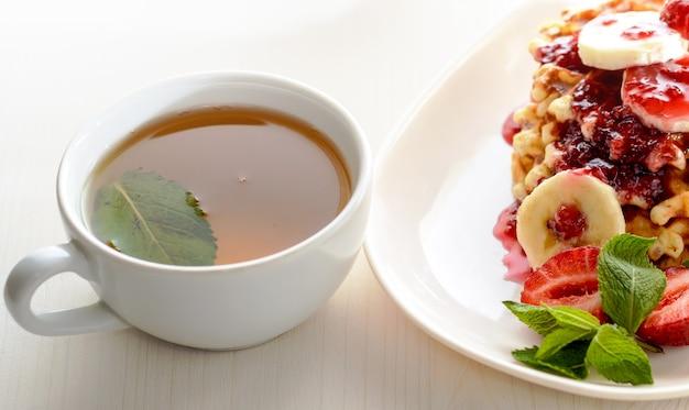 Postre de gofres con fresas, plátanos y menta. taza de té para un desayuno saludable