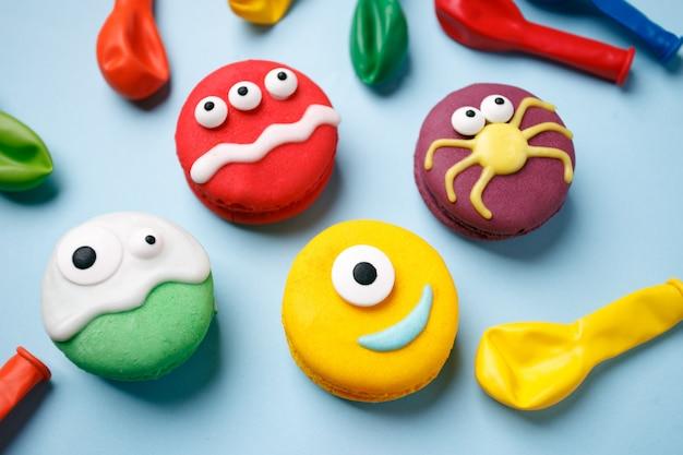 Postre de heloween: monstruos divertidos hechos de galletas macarrón con glaseado y dulces ojos de primer plano sobre la mesa.