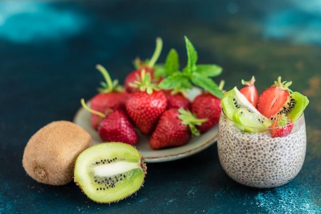 Postre hermoso y sabroso con un kiwi, fresa y semillas de chia