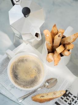Postre italiano tradicional de la almendra de biscotti con la taza de café y el pote del café de moka en el periódico.