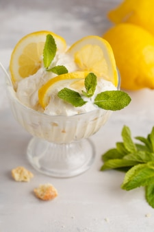Postre de limon torta de limón inglesa, tarta de queso, crema batida, parfait. mousse de frutas en vidrio sobre un fondo claro.