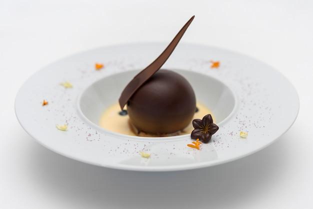 Postre de lujo con globo de chocolate y salsa de vainilla, servido en una galleta, con chocol