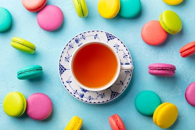 Postre de macarrones y taza de té. composición plana laica. vista superior.
