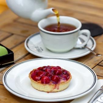 Postre de masa quebrada con bayas y una taza de té aromático