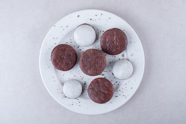 Postre de mini mousse de hojaldre y galleta bañada en cholate en un plato, sobre el mármol.
