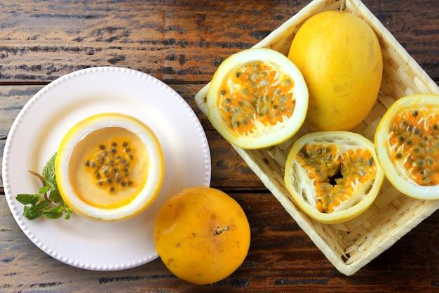 Postre mousse de maracuyá en cáscara de fruta en plato que adorna la mesa de madera rústica