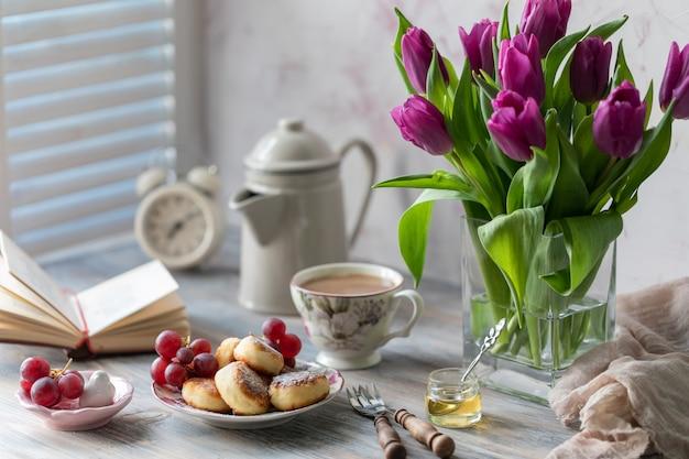 Postre de requesón, pasteles de queso sobre la mesa con un ramo de tulipanes, relojes y frutas en una mesa de madera junto a la ventana.
