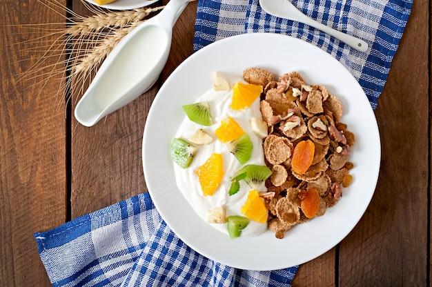 Postre saludable con muesli y fruta en un plato blanco sobre la mesa