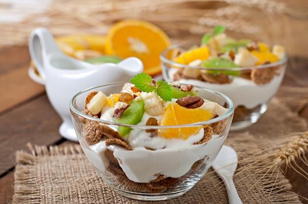 Postre saludable con muesli y fruta en un recipiente de vidrio sobre la mesa