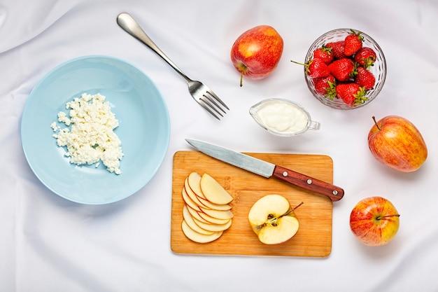 Postre saludable con requesón y fresas en plato azul sobre un mantel blanco