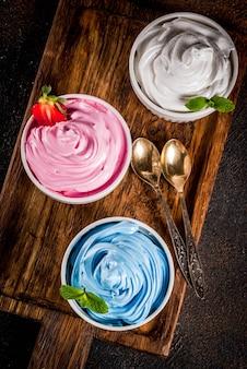 Postre saludable de verano, yogurt helado de vainilla y bayas o helado suave en tazones blancos