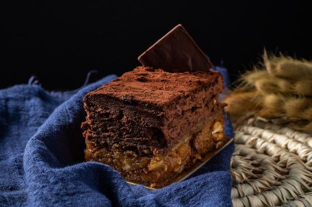 Postre sofia con capas de mousse de chocolate y cacahuetes caramelizados cubiertos de cacao en polvo.