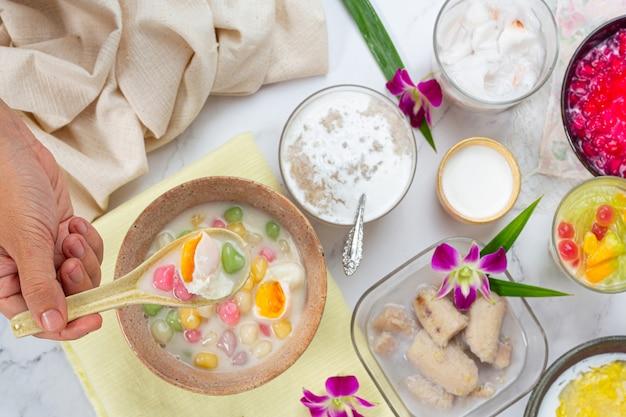 Postre tailandés llamado bolas de bualoy en salsas con leche de coco caliente y hojas de pandan para aumentar la delicia.