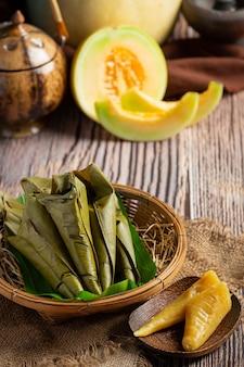 Postre tailandés. pasteles de melón al vapor envueltos en cono de hoja de plátano