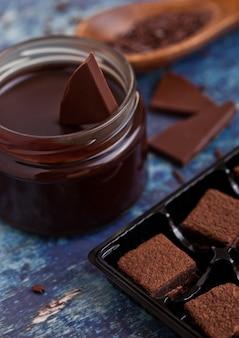 Postre de tarta de galletas de chocolate en tablero azul con frasco de chocolate líquido y cuchara de madera