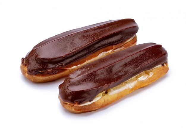 Postre tradicional francés. aislado dos eclairs con crema pastelera y chocolate glaseado sobre fondo blanco.