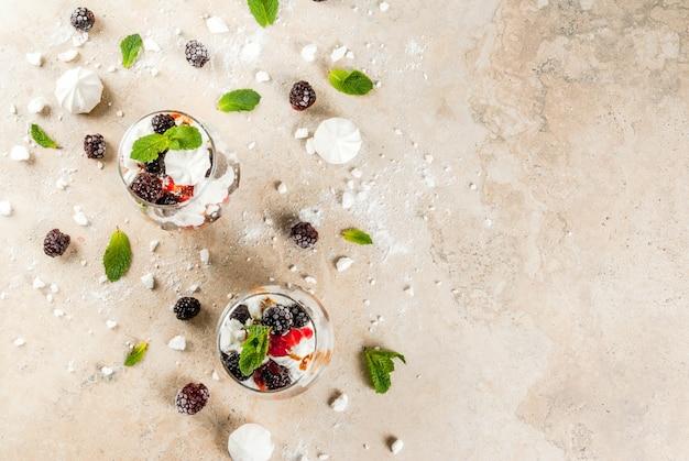 Postre tradicional inglés. eton mess: crema batida, merengue, moras frescas, salsa y caramelo. en servir vasos en una mesa de piedra clara. copia espacio vista superior