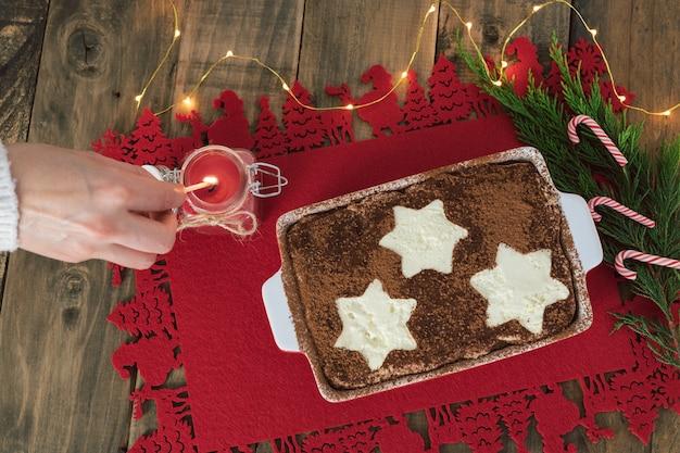 Postre tradicional italiano. tiramisú decorado con estrellas y mano encendiendo una vela. decoración navideña. copie el espacio.