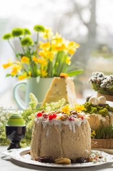 Postre tradicional ruso de requesón de pascua, paskha ortodoxa en la mesa con pasteles de kulich, flores, huevos de colores.