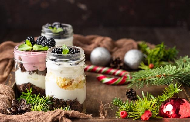 Postres en capas con pastel, crema batida y moras sobre fondo de navidad