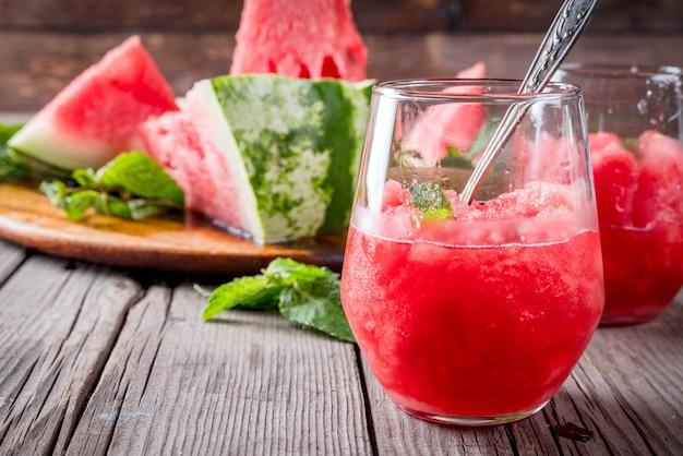 Postres de frutas de verano, cócteles congelados. helado de granito de sandía con menta, en vasos en porciones, con rodajas de sandía.
