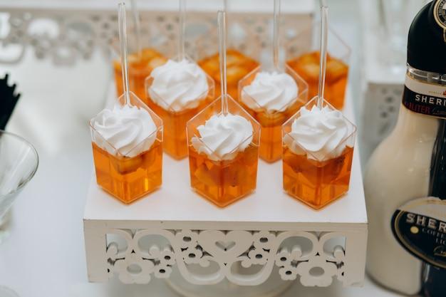 Postres de gelatina de naranja con crema batida en una bandeja blanca