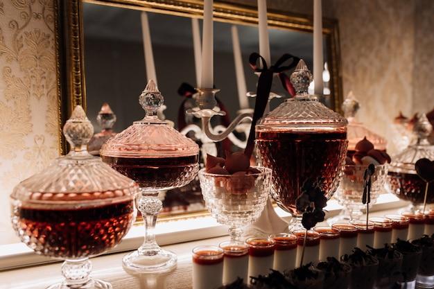Postres de mousse de chocolate, pana cotta y ponche rojo en la cristalería
