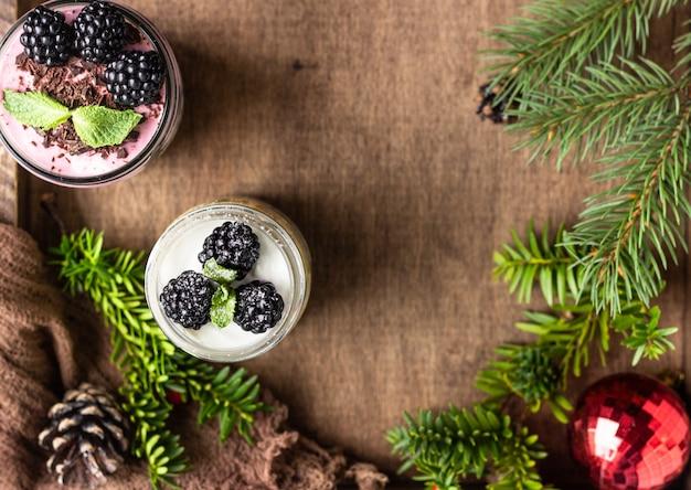 Postres navideños en capas con pastel, crema batida y moras