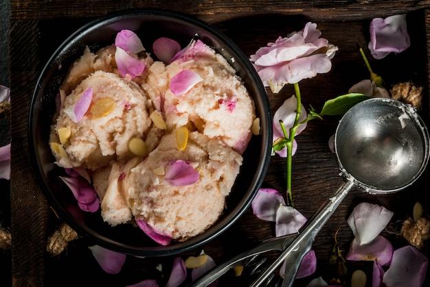 Postres refrescantes de verano comida vegana de dieta helado con pétalos de rosa y rodajas de almendras en una bandeja de madera vieja en una mesa de piedra negra con una cuchara para helado e ingredientes
