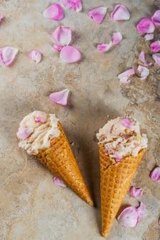 Postres refrescantes de verano comida vegana dietética helado con pétalos de rosa y rodajas de almendras en clásicos conos de helado de gofres sobre una mesa de hormigón beige claro