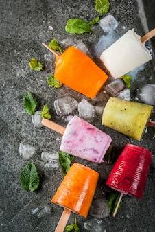 Postres saludables de verano. paletas de helado. jugos tropicales congelados, batidos de arándanos. grosellas, naranja, mango, kiwi, plátano, coco, frambuesa. en la mesa de piedra negra copia espacio vista superior