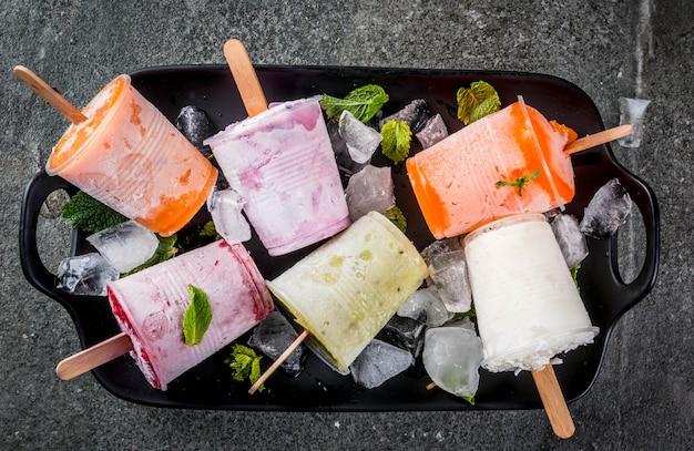 Postres saludables de verano. paletas de helado. jugos tropicales congelados, batidos de arándanos. grosellas, naranja, mango, kiwi, plátano, coco, frambuesa. en la mesa de piedra negra, vista superior del espacio de copia de placa
