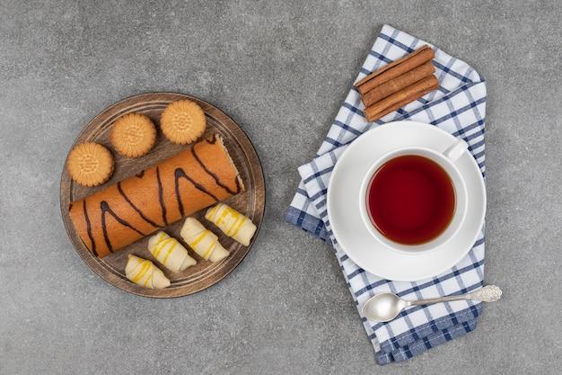 Postres, taza de té y palitos de canela en la superficie de mármol