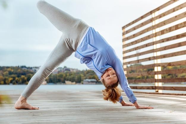 Posturas de yoga, la joven levanta fácilmente la pierna en la postura de yoga del perro boca abajo